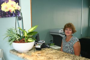 Diane Meehleis sitting at the front desk at Dover Dental